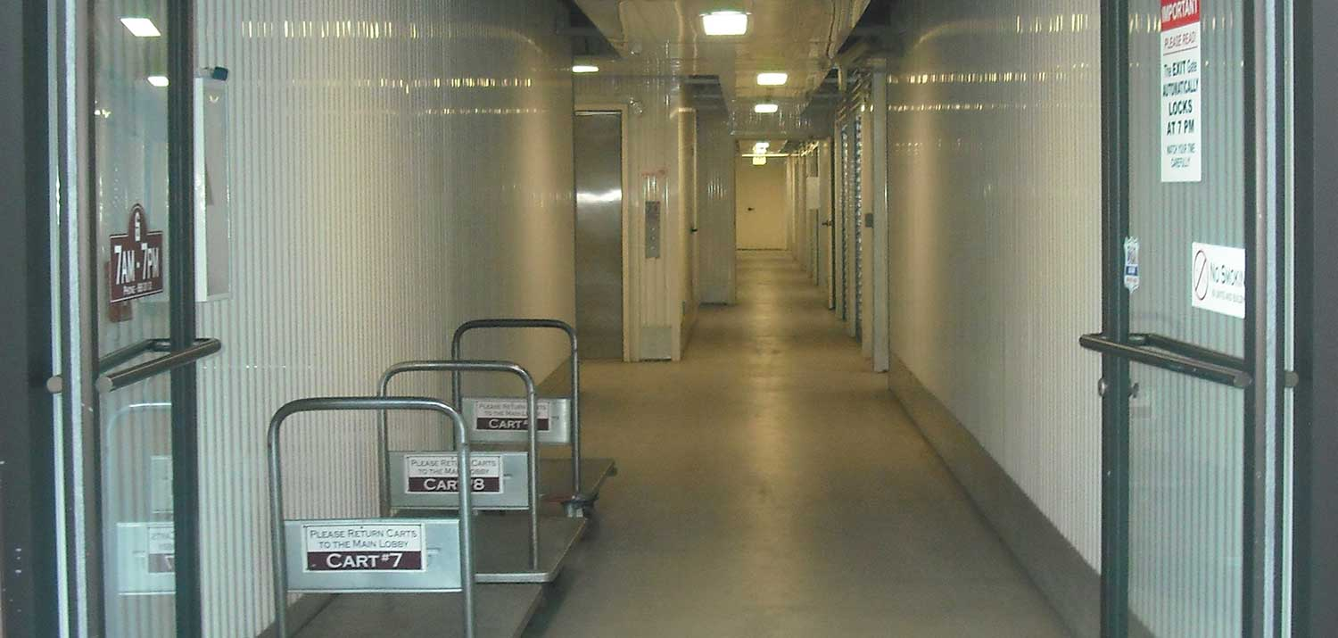 View of facility hallway with carts and elevator